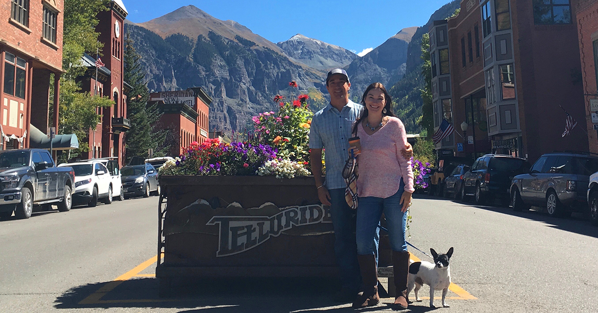Colorado home inspector David Pace standing with his wife and dog in front of mountains and a small town.