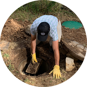 Person with yellow gloves and work boots opening up the cover of a septic tank.